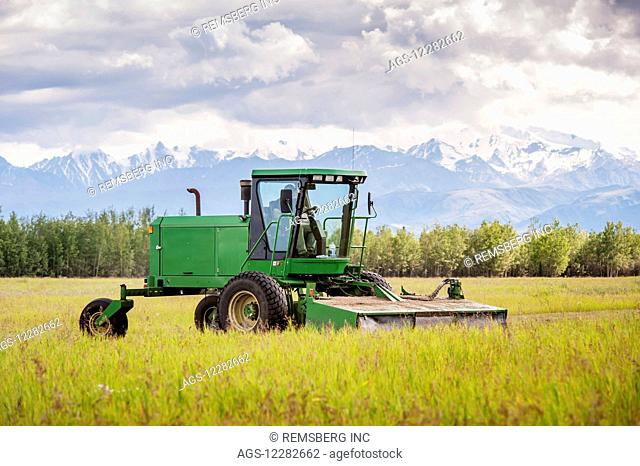 Self propelled disc mower cutting a field of hay (grass); Delta Junction, Alaska, United States of America