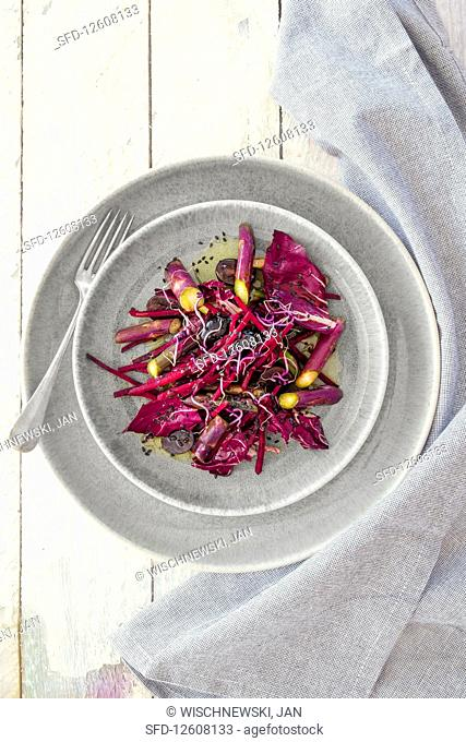 A salad with purple asparagus, beetroot, grapes and radicchio