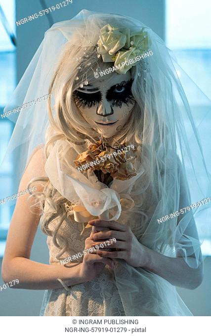 Halloween witch. Beautiful bride woman wearing santa muerte mask and wedding dress holding dead bouquet of roses