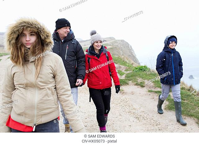 Family in warm clothing walking on snowy winter cliff path