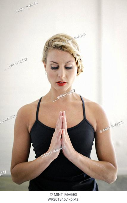 A blonde woman in a black leotard doing yoga, standing with her eyes closed and her hands together