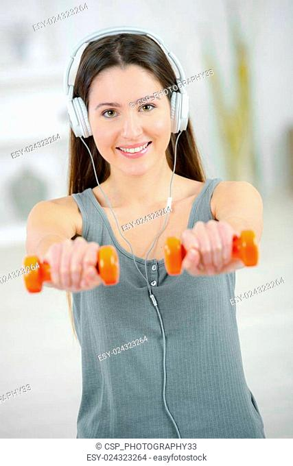 Woman lifting weights whilst listening to music