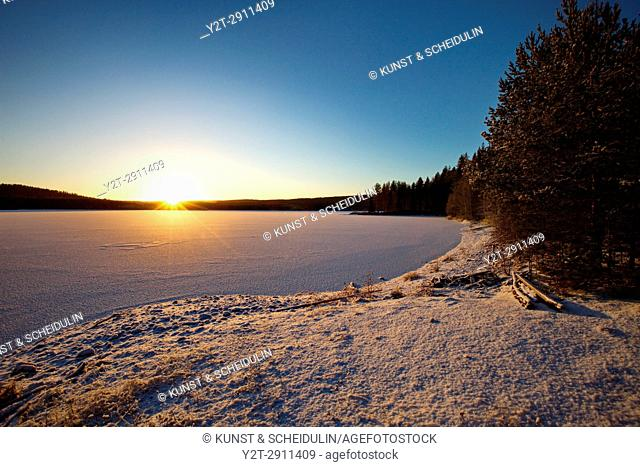 An ice covered lake in northern Sweden is illuminated by the low winter sun. Agnsjön, Bredbyn, Västernorrland, Sweden