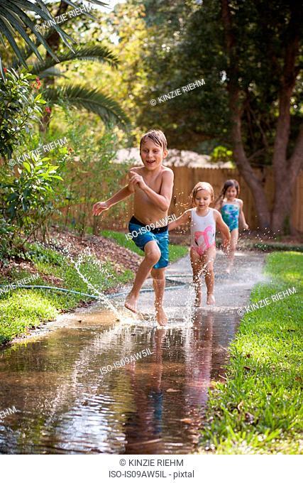 Children running in water on sidewalk