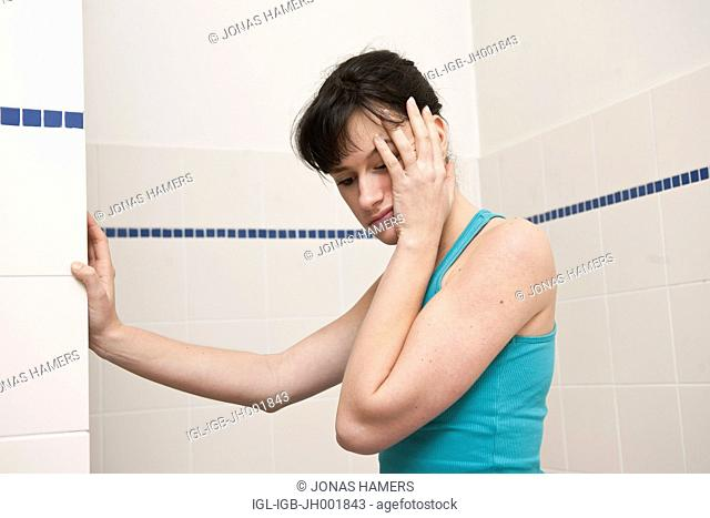 This picture shows a young caucasian woman with brown hair in her bathroom feeling ill or sick, tired or anxious