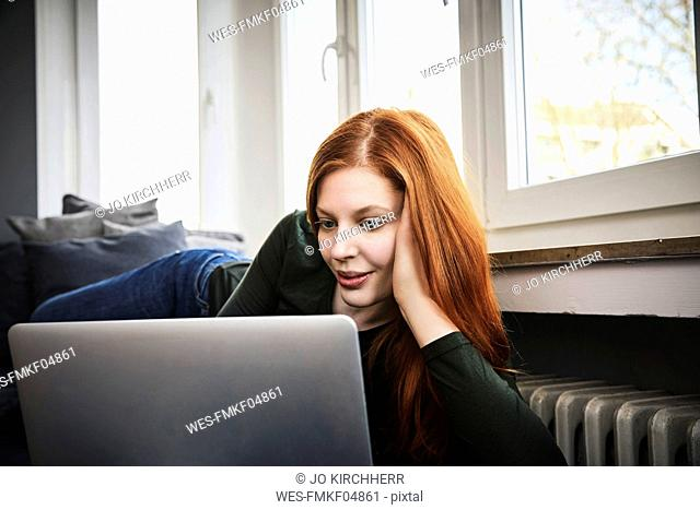 Portrait of redheaded woman using laptop at home