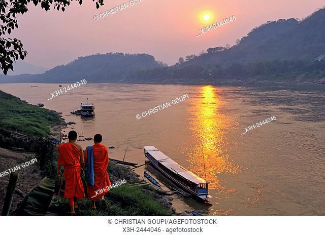 monks at sunset on Mekong River at Luang Prabang, Laos, Southeast Asia