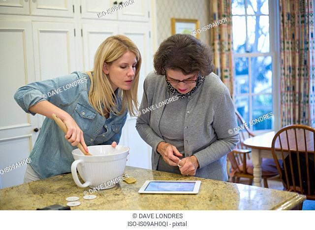 Senior woman and granddaughter baking and using digital tablet