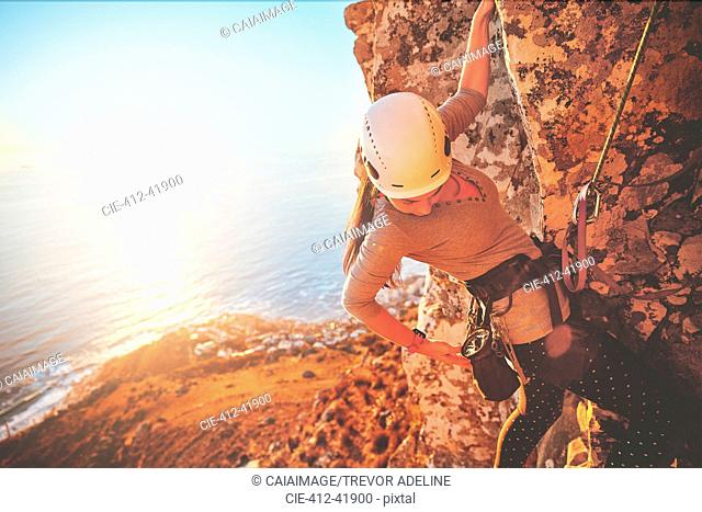 Female rock climber reaching for clip above sunny ocean
