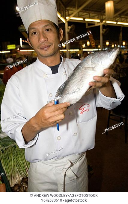 Chef displays fresh iced fish from seafood display at outdoor restaurant Anusan Market in Chiang Mai Night Market north Thailand