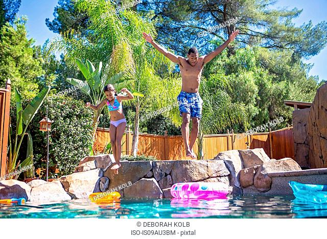 Full length front view of father and daughter mid air jumping into swimming pool