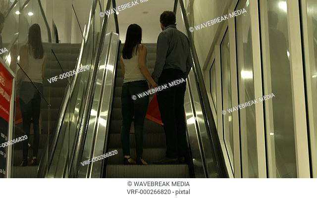Back view of couple standing in escalator