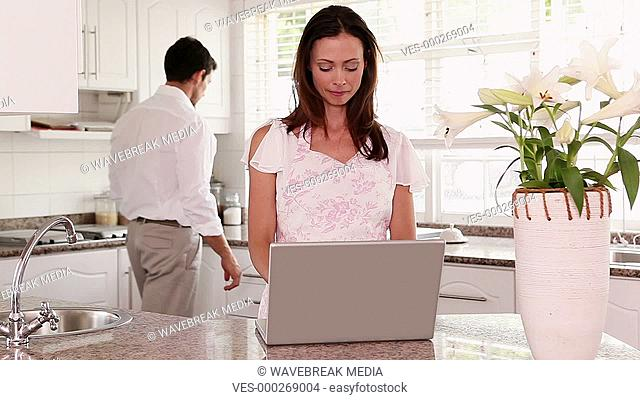 Pretty woman using laptop at the counter