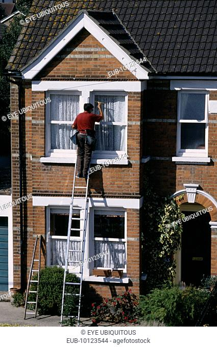 Window cleaner on ladder cleaning outside of household windows