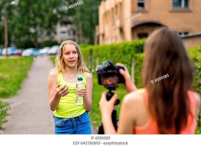 Two girls teenage girlfriends, in the city on nature in the summer. In her hands holds a bottle of water and a green apple. Record video on the camera