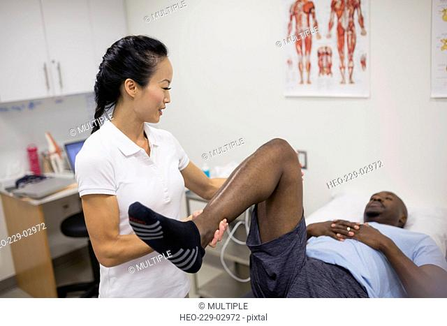 Physical therapist stretching patient leg in examination room