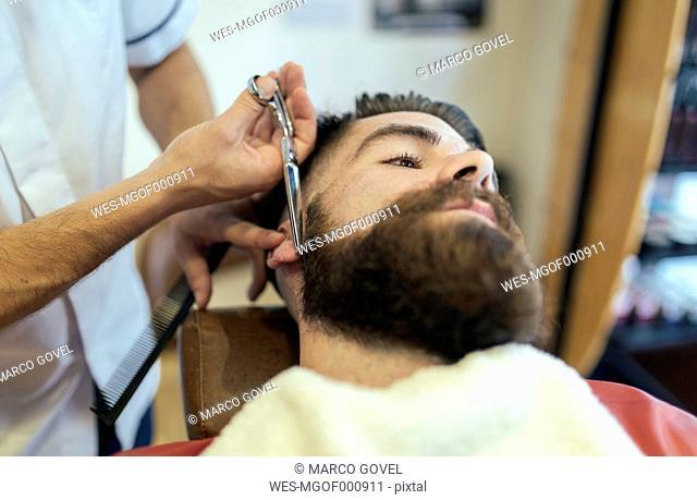 Barber cutting beard of a customer
