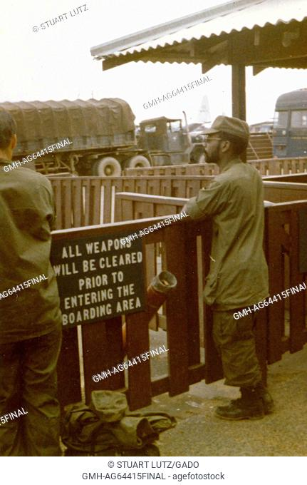 Two soldiers in uniform can be seeing leaning on a wooden fence while they are awaiting transport at an air terminal, a sign in the foreground instructs...