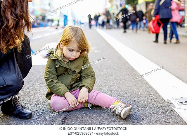 three years old blonde lovely caucasian girl child, with crying and sad expression and tear in face, next to mother, sitting on grey asphalt at pedestrian Gran...