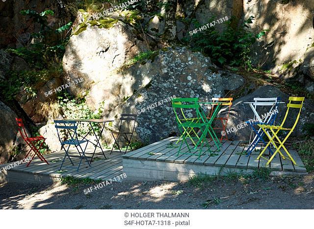 Schweden, Insel Grinda, leere Stühle auf Holzterrasse