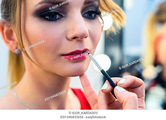 close up view of Make-up artist painting red lips makeup to beautiful young girl in the studio. Red lipctick painting. Beauty picture