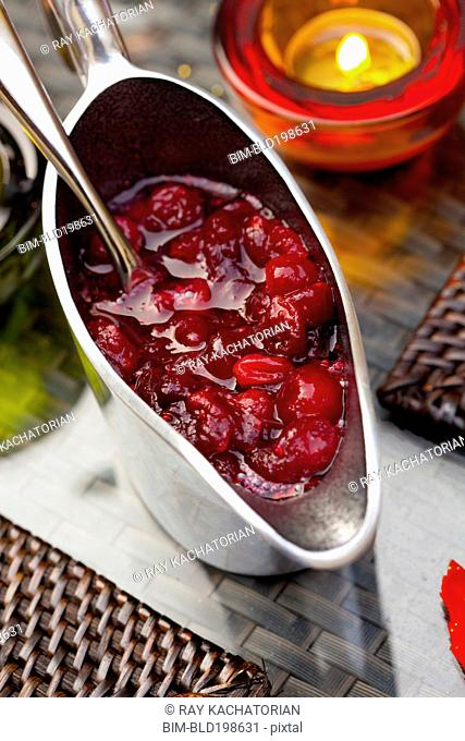 Cranberry sauce in pitcher on table