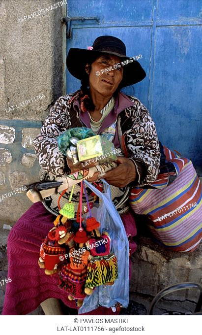A woman of the ethnic minority Quechua Indian group wearing a black hat offering souvenirs and craft goods for sale. Dolls