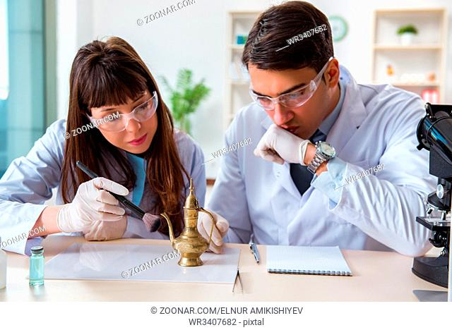Two archeologists looking at ancient gold lamp