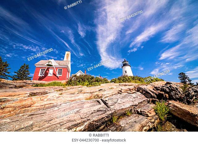 Pemaquid Point Lighthouse on dramatic rocky coast in Bristol, Maine, on a beautiful summer day