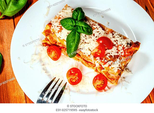 Italian lasagne with tomato and vegetables and chesse on wood table