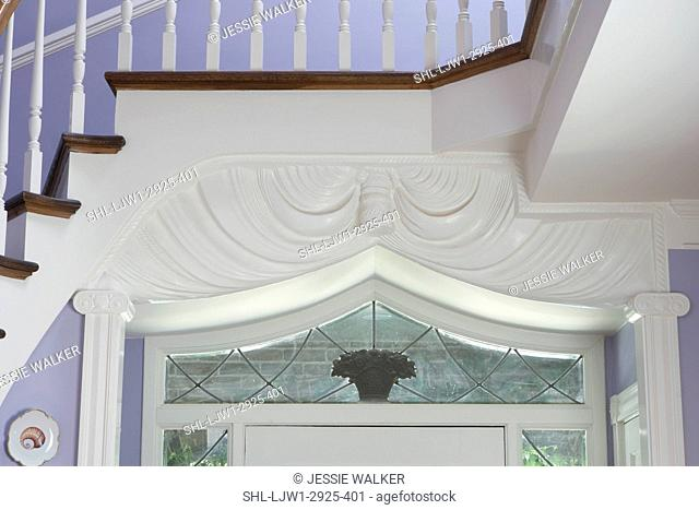 Architectural detail: View of top section of passageway surround. Pilasters and columns. Stairway crosses over entryway. White woodwork and lavender walls
