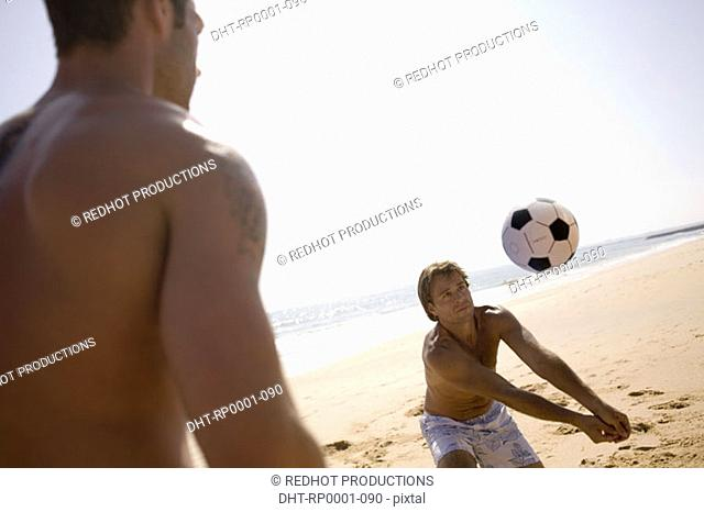 Two men playing with ball on beach