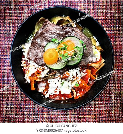 Red and green chilaquiles for breakfast with grilled meat in Jaguar Yuu restaurant in Oaxaca, Mexico