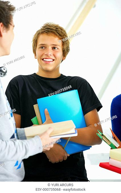 Young student holding a stack of books while talking to a friend