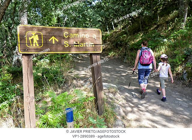 Two hikers, a woman and a young girl, walk the Path of the Monks. Signage of the Path of the Monks. Old Ribadelago. Natural Park of the Lake of Sanabria
