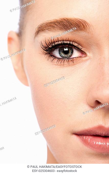 Beautiful eye with eyebrow and lashes on half face of attractive young woman