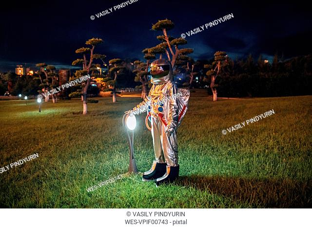Spaceman standing at a lamp in a park at night
