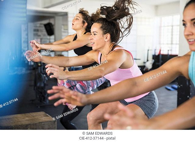 Energetic young women riding elliptical bikes in exercise class
