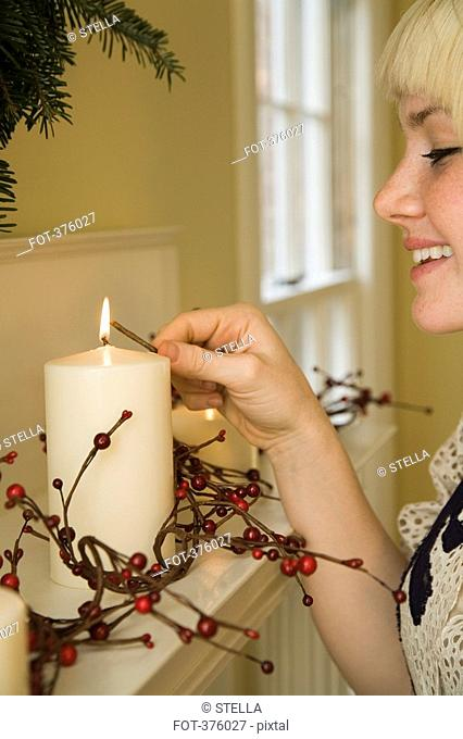 Young woman lighting candles on a mantelpiece