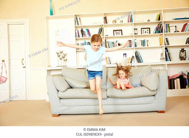 Two young sisters jumping from and bouncing on sofa