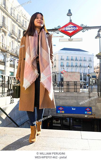 Spain, Madrid, smiling young woman at Puerta del Sol metro station