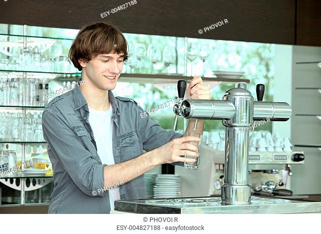 Barman pouring pint