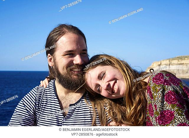 happy girlfriend leaning on her boyfriend's shoulder and enjoying vacations, next to the sea in Gozo, Malta, Europe