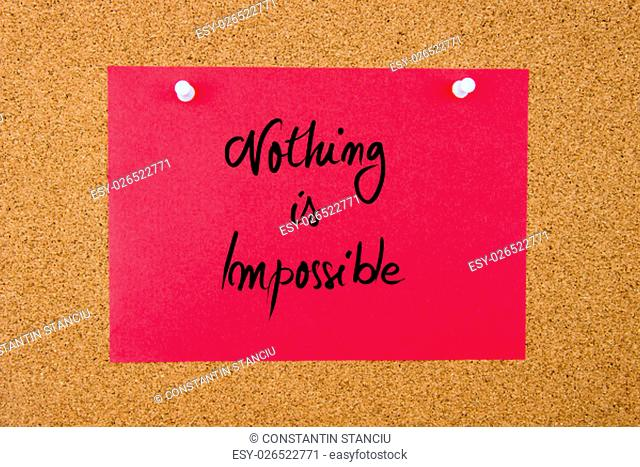 Red paper note with handwritten text Nothing Is Impossible pinned on cork board with white thumbtacks