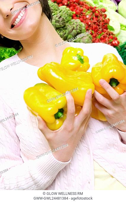 Woman holding yellow bell peppers in a supermarket