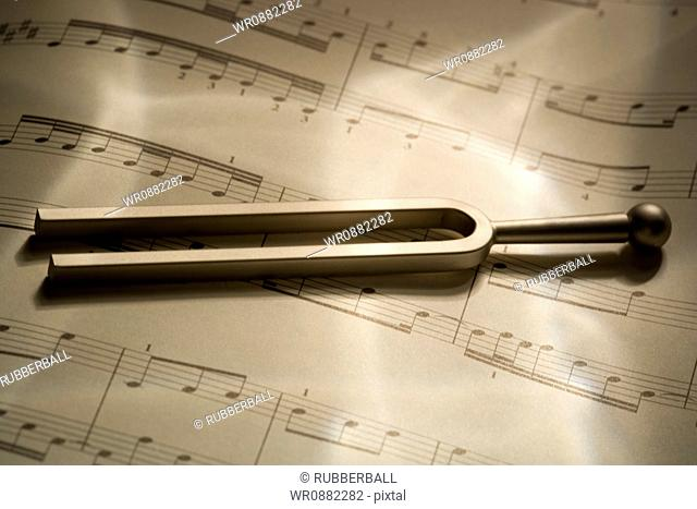 Close-up of a tuning fork and music sheets