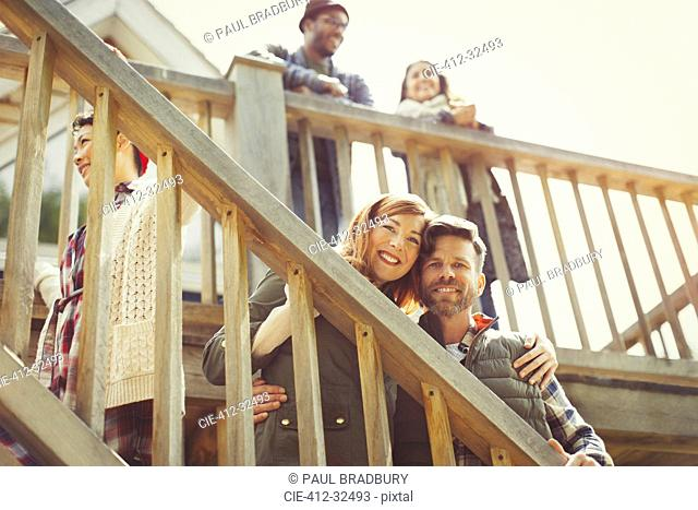 Portrait smiling couple on stairs outside cabin
