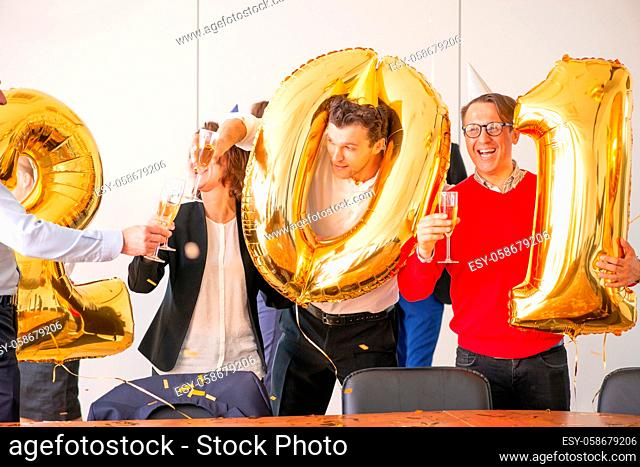 Business people are celebrating holiday in modern office drinking champagne and having fun in coworking. Merry Christmas and Happy New Year 2020 concept