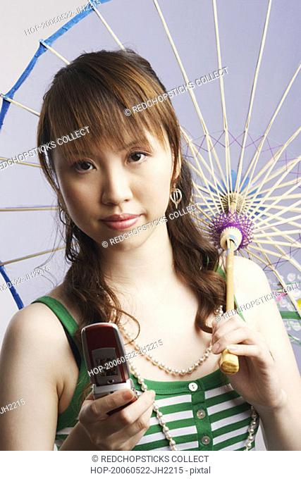 Portrait of a young woman holding a parasol and a mobile phone