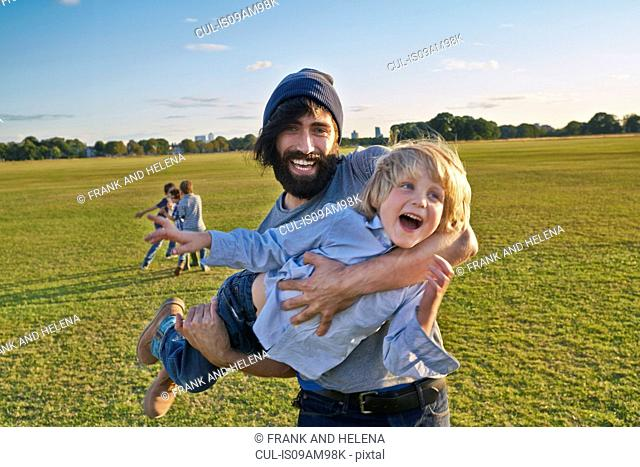 Mid adult man carrying son in field